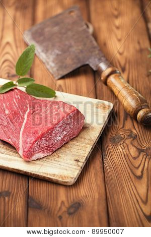 raw beef meat fillet  on wooden  table with meat cleaver and 1lb iron weight stock photo